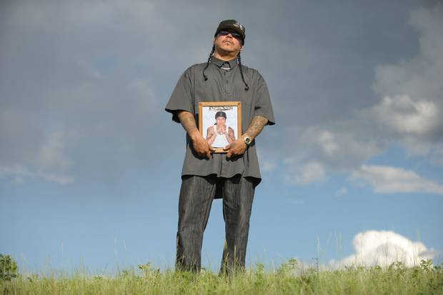 Richard Wolfe holds a photo of his late brother, Daniel Wolfe, on a hilltop near Richard's home in Fort Qu'Appelle, Sask., in 2011.