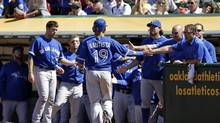 Jose Bautista is greeted by his Toronto Blue Jays teammates after scoring a run in the 10th inning in Oakland on Wednesday. (Eric Risberg/The associated Press)