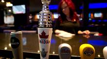 A miniature Stanley Cup is seen on a beer tap as bartender Julia Proulx cleans up at Forum Sports Bar on Granville St. in downtown Vancouver, B.C., on April 23, 2012. (Darryl Dyck For The Globe and Mail)