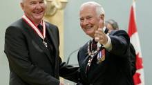 John Furlong of Vancouver, left, chief executive officer of the Vancouver Organizing Committee of the 2010 Winter Olympics, shakes hands with Governor-General David Johnston after he was invested into the Order of Canada in September 2011. (Fred Chartrand/The Canadian Press)