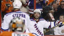 New York Rangers' Martin St. Louis, right, looks to celebrate his goal with Derek Stepan, middle, as Philadelphia Flyers goalie Ray Emery watches during the first period in Game 3 of an NHL hockey first-round playoff series, Tuesday, April 22, 2014, in Philadelphia. (Associated Press)
