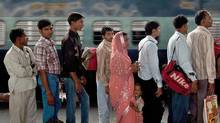 A lone Indian woman stands in line at the railway station in New Delhi. As the global population hits seven billion, experts are warning that skewed gender ratios could fuel the emergence of volatile 'bachelor nations' driven by an aggressive competition for brides. (MANAN VATSYAYANA/AFP/Getty Images)
