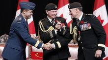 Passing the torch: Gen. Tom Lawson, left, shakes hands with his predecessor, Gen. Walt Natynczyk, right, to he delight of Governor-General David Johnston during the change-of-command ceremony in Ottawa two weeks ago. (CHRIS WATTIE/REUTERS)