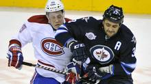 The Winnipeg Jets' Dustin Byfuglien checks the Montreal Canadiens' Andrei Kostitsyn during the third period on Dec. 22, 2011. Both teams are on the outside looking in as the playoff race heats up. (Fred Greenslade/Reuters/Fred Greenslade/Reuters)