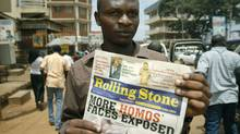 A November 2010 file photo shows the editor of Uganda?s Rolling Stone newspaper, Giles Muhame, holding an issue of the publication in a street of Kampala. (Marc Hofer/AFP/Getty Images)