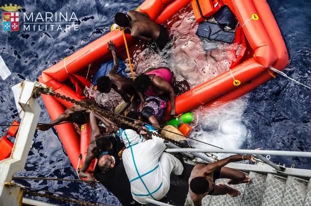 In this photo taken May 27, 2016, in the Mediterranean off the Libyan coast, rescuers help migrants to board the Italian Navy ship Vega after the boat they were aboard sunk.