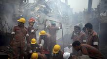 Workers and fire fighters are shrouded in smoke as they prepare to dislodge the debris and fallen ceiling of the garment factory building which collapsed in Savar, near Dhaka, Bangladesh on Monday, April 29, 2013. (Wong Maye-E/AP)
