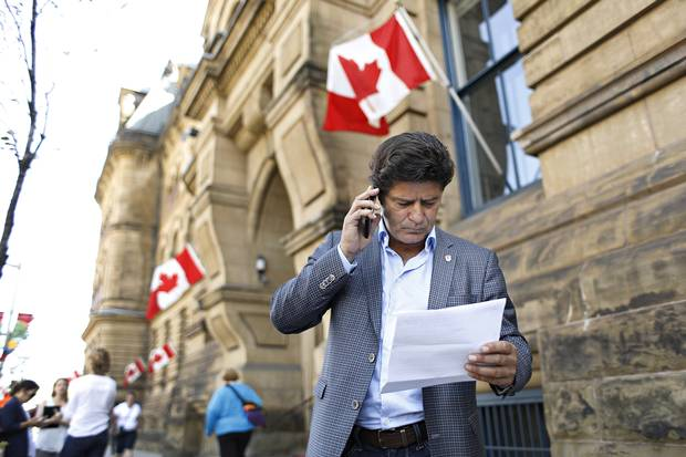 Jerry Dias reads a copy of an article given to him from a member of the PMO outside Langevin Block.