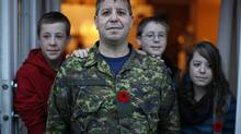 Master Warrant Officer Paul Watkins at home in Courtney, B.C., with his children, from left, Danny, 15, Kyle, 14, and Chelsea, 17. MWO Watkins's oldest son, Scott, is currently in military training in Quebec. (CHAD HIPOLITO For The Globe and Mail)