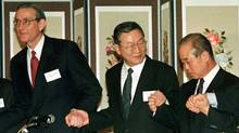 William (Bill) Rhodes, left, clasps hands with South Korean finance minister Lee Kyu-sung, centre, and chairman of the Korea Exchange Bank Hong Se-pyo in a show of unity after a signing ceremony for debt extension in Seoul, March 31, 1998. (Paul Barker/Reuters/Paul Barker/Reuters)