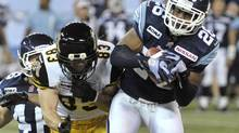 Toronto Argonauts defensive safety Jordan Younger (R) intercepts a pass intended for Hamilton Tiger-Cats wide receiver Andy Fantuz during the first half of their CFL football game in Toronto November 1, 2012. REUTERS/Mike Cassese (CANADA - Tags: SPORT FOOTBALL) (MIKE CASSESE/REUTERS)