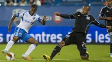 San Jose Earthquakes' Victor Bernardez, right, slides in on Montreal Impact's Patrice Bernier during first half MLS soccer action in Montreal, Saturday, August 18, 2012. (The Canadian Press)