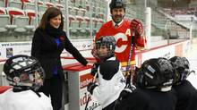 Rona Ambrose, left, Minister of Health, and former Calgary Flames player Jamie Macoun, meet with minor hockey players at an announcement regarding support for research on injury prevention in Calgary, Alta., Monday, Nov. 4, 2013. (Jeff McIntosh/THE CANADIAN PRESS)