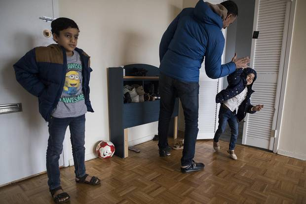 Ali Al-Dhamadi gets ready to go outside with his daughter Alya 5, and son Taha, 10, in Toronto on Nov. 21, 2017.