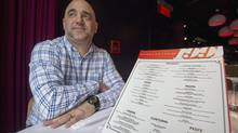 Massimo Lecas, co-owner of Buonanotte restaurant, poses for a photograph with a menu at the restaurant in Montreal, on February 20, 2013. The head of Quebec's language watchdog agency resigned Friday following a series of controversies that have created embarrassing headlines at home and abroad. (Graham Hughes/The Canadian Press)