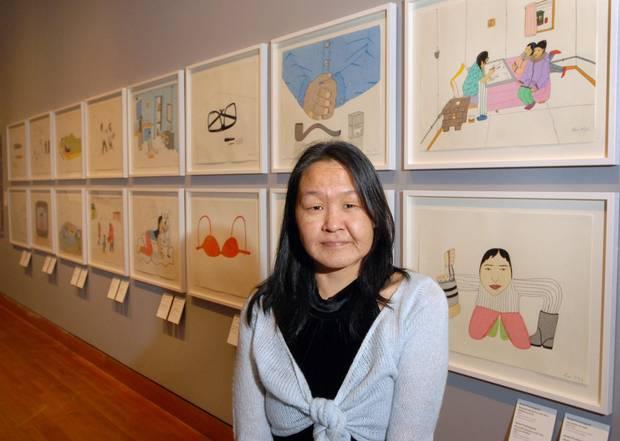 Annie Pootoogook in front of her artwork.