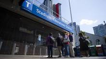 Commuters are stopped by a gate at the Stadium-Chinatown station during a lengthy delay in service. (Ben Nelms/The Globe and Mail)