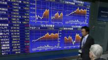 A man watches an electronic stock indicator in Tokyo, Tuesday, Oct. 29, 2013. (Shizuo Kambayashi/AP)