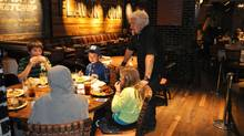 Guy Fieri talking to patrons at his Guy's American Kitchen and Bar in New York.