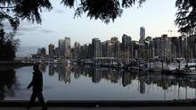 Walking the Stanley Park seawall as the Vancouver skyline is reflected in the waters off Coal Harbour on Feb. 5, 2010. (Jae C. Hong/The Associated Press)