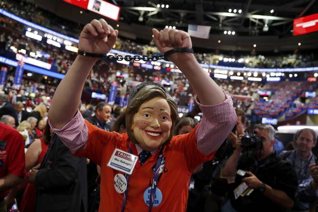 A delegate wearing a mask of Democratic presidential candidate Hillary Clinton, as well as handcuffs and a prison jumpsuit, appears on the convention floor.