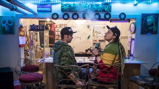 Nathan Adams, left, vice-president of the Calgary Cannabis Society and his wife, Lisa Kirkman, the president of the group, sit at the bar and share a smoke during 4/20 events in Calgary.
