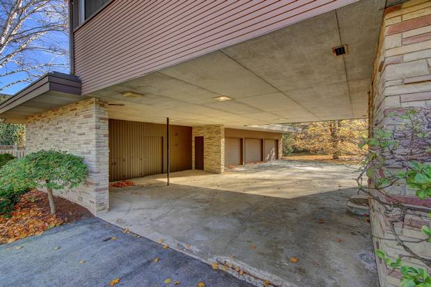 The garage is accessed via a carport under the home's second storey.