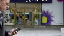 A cellphone user passing a Telus store in Toronto. (Peter Power/The Globe and Mail)