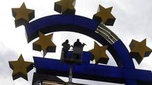 Workers maintain the huge Euro logo next to the headquarters of the European Central Bank (ECB) in Frankfurt. (RALPH ORLOWSKI/REUTERS)