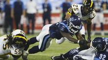 Toronto Argonauts Cory Boyd (C) runs the ball in for a touchdown with teammate Andre Durie (R) past Hamilton Tiger-Cats Markeith Knowlton and Stevie Baggs (L) during the second half of their CFL football in Toronto, November 3, 2011. (MARK BLINCH/REUTERS)
