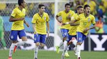 Brazil's Neymar celebrates with teammates after scoring during the group A World Cup soccer match between Brazil and Croatia, the opening game of the tournament, in the Itaquerao Stadium in Sao Paulo, Brazil, Thursday, June 12, 2014. (Andre Penner/AP)