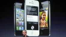 Apple CEO Tim Cook speaks in front of an image of the iPhone 4S. (ROBERT GALBRAITH/REUTERS)