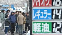 People wait in line in front of a closed petrol station to get a number to be able to get fuel later in the day in the town of Tonoi on March 17, 2011, six days after a major earthquake and tsunami hit the northeastern coast of Japan. (NICHOLAS KAMM)