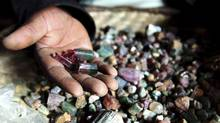 A Congolese mineral trader displays semi-precious tourmaline gem stones in a mud hut at Numbi in eastern Congo July 24, 2010. Efforts to clamp down on Congo's armed groups that finance their existence with minerals sourced from the country's conflict-wracked east -- much of which ends up in laptops, cell phones and jewellery around the world -- have been criticised for trying to achieve the impossible and risking the livelihoods of a million people in the area who depend on mining. (© Katrina Manson / Reuters/Katrina Manson/Reuters)