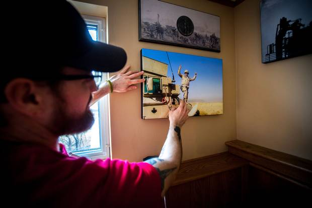 """Mr. McNeil displays a photo in his basement from the day he hit the IED in Afghanistan that caused his brain injury. 'I don't even remember the photo being taken,' he says. 'My buddy just said """"smile, you're alive"""" and snapped this picture when I finally got out of the vehicle.'"""