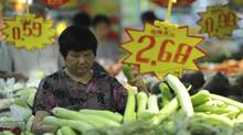 A woman picks vegetables at a supermarket in Hefei in central China's Anhui province Thursday, Aug. 9, 2012. (AP)