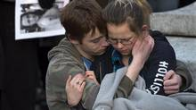 Friends embrace as several hundred people attend a community vigil to remember Rehtaeh Parsons at Victoria Park in Halifax. The girl's family says she ended her own life last week following months of bullying after she was allegedly sexually assaulted by four boys and a photo of the incident was distributed. (Andrew Vaughan/THE CANADIAN PRESS)
