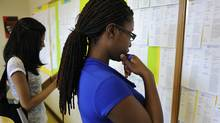Zohra Surani,21, left and Melinda Cuffy, 23, pore over jobs listings at the Summer Jobs Services centre at 511 Richmond S.t West in downtownToronto. (Fred Lum/The Globe and Mail)