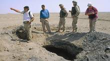 A freshly-dug looter's pit draws the interest of archaeologist Henry Wright, left, of the University of Michigan, as he surveys an ancient site in Iraq, on May 18, 2003, near the ancient southern Mesopotamian city of Larsa. Some ancient sites where civilization began, have been looted and badly damaged but others remain well-guarded, according to a team of researchers led by Wright, who conducted the first archaeological survey outside Baghdad since the war ended. From left to right are: Wright, an unidentified Iraqi driver, U.S. Marine Maj. Glenn Sadowski, an unidentified Marine from the 225th Marine battalion, and team member Elizabeth Stone, an archaeologist based at Stony Brook University in New York. (STEVE MCCURRY/AP)