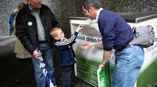 Isaac Liljegren, 6, drops the ballot of his dad Eric Liljegren, left, and the ballot of his other dad Scott Shiebler, right, into a ballot drop box outside the King County Administration Building in Seattle. (Joshua Trujillo/AP)