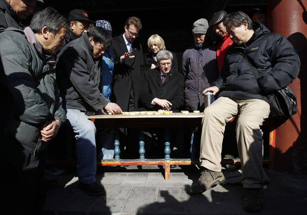 Mark Rowswell, centre left, is seen with then prime minister Stephen Harper and his wife Laureen, as they watch a game of chess while touring the Temple of Heaven in Beijing in 2012.