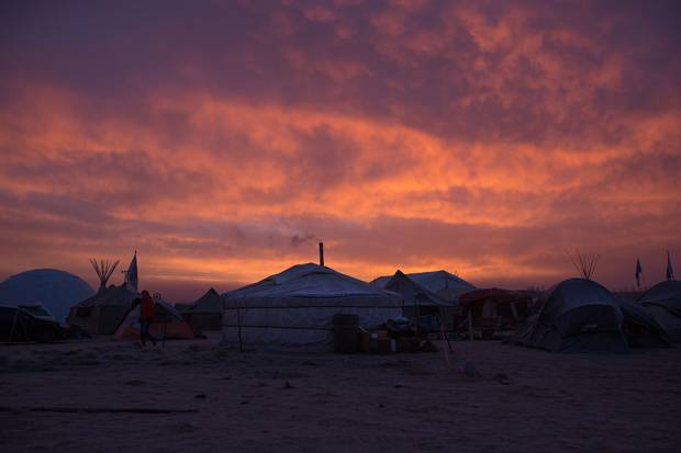 The sun rises over a frosty camp near Cannon Ball at the end of November. Yurts, tepees, military structures, tiny homes, trailers, wigwams and other improvised structures are in use for winter shelter.