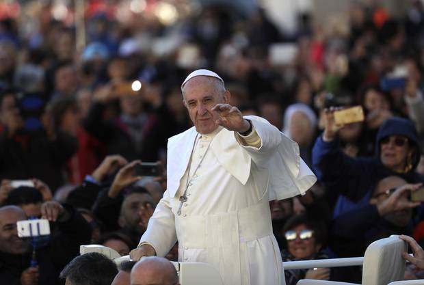 Pope Francis waves as he is driven across the crowd ahead of his weekly general audience in St. Peter's Square at the Vatican on Nov. 9, 2016.