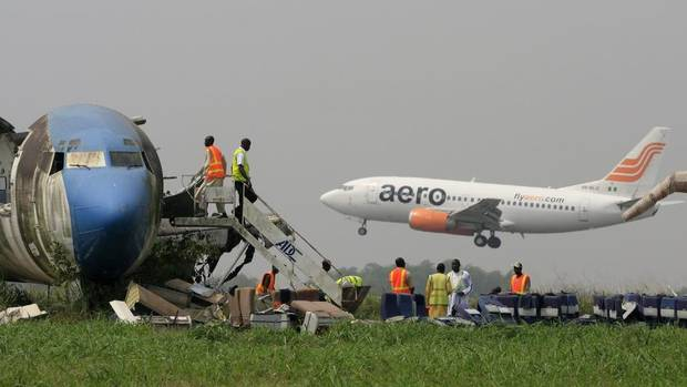 A passenger plane lands as workers dismantle an abandoned aircraft at Murtala Muhammed International Airport in Lagos, Jan. 31, 2013. Nigerian aviation officials are dismantling and removing the hulks of abandoned aircraft from airports around the country. (Jon Gambrell/AP)