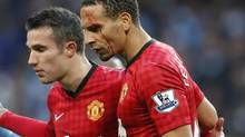 Manchester United's Rio Ferdinand (R) is helped from the pitch by teammate Robin van Persie after being struck by an object thrown from the crowd during their English Premier League match against Manchester City at The Etihad Stadium in Manchester, northern England December 9, 2012 (PHIL NOBLE/REUTERS)