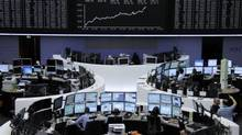Traders are pictured at their desks in front of the DAX board at the Frankfurt stock exchange on August 3. (TOBIAS SCHWARZ/REUTERS)