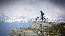 A mountain biker stops part way down the Top of the World trail to take in the view. (John Lehmann/The Globe and Mail)