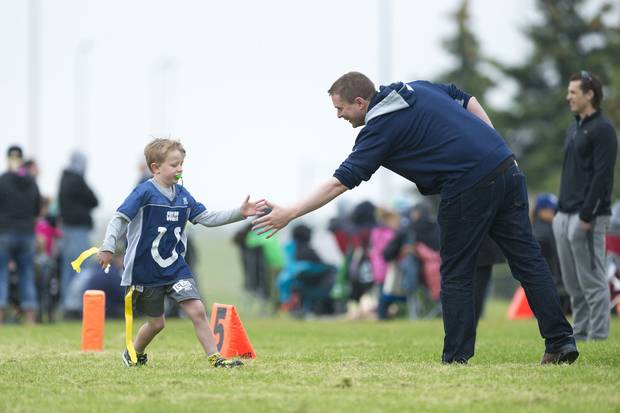 Conservative Leader Andrew Scheer high-fives his son Henry after a good play during a football game at the University of Regina campus.