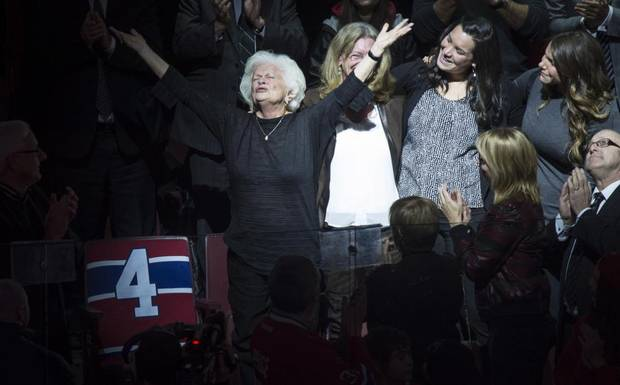 Elise Beliveau salutes the crowd as she stands next to her husband Montreal Canadiens legend Jean Beliveau's empty seat, during a ceremony prior to facing the Vancouver Canucks in NHL hockey action Tuesday.
