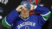 Bo Horvat tries on his Vancouver Canucks jersey and cap after being selected by the Canucks as the ninth overall pick in the 2013 National Hockey league (NHL) draft in Newark, New Jersey, June 30, 2013. (Reuters)